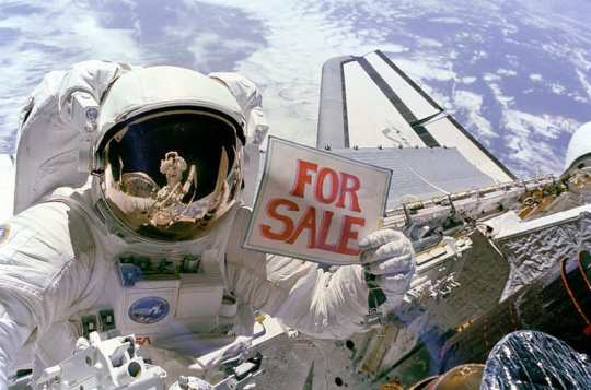 "Astronaut Dale A. Gardner holds up a ""For Sale"" sign refering to two satellites."